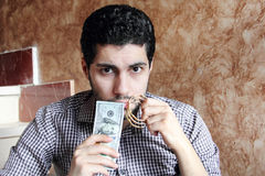 Arab young businessman with dollar bills money and gold jewelry. Arab young muslim business man feeling confused with dollar bills and gold jewelry in his hands Royalty Free Stock Photos