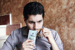 Arab young businessman with dollar bills money and gold jewelry. Arab young muslim business man feeling confused with dollar bills and gold jewelry in his hands Royalty Free Stock Photography