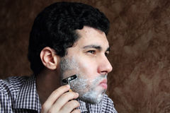 Arab  young businessman shaving his beard with a razor Stock Image