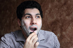 Arab  young businessman shaving his beard with a razor Stock Photo