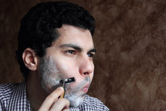 Arab  young businessman shaving his beard with a razor Royalty Free Stock Photography