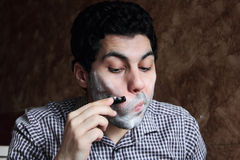 Arab  young businessman shaving his beard with a razor Stock Images