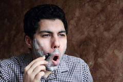 Arab  young businessman shaving his beard with a razor Stock Photography