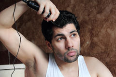 Arab young man cutting hair with hair clipper royalty free stock photo