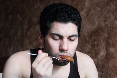 Arab young man eating chocolate nutella Stock Photo