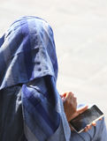 Arab young woman with veil and smart phone. In town Stock Photo