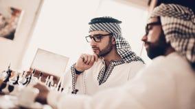 Arabe avec des verres prévoyant la stratégie dans les échecs photo libre de droits