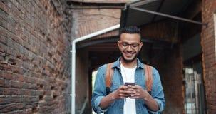 Arabe barbu bel appréciant l'application moderne de smartphone souriant dehors banque de vidéos