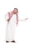 Arabe dans une robe longue blanche faisant des gestes avec sa main Photographie stock