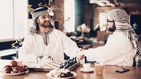 Arabe deux se serrant la main avant de jouer aux échecs photos libres de droits