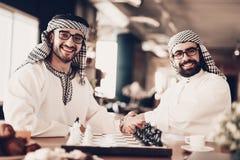 Arabe deux se serrant la main avant de jouer aux échecs photo stock