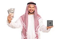Arabe tenant l'argent et un petit coffre-fort en métal photo stock