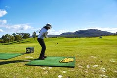 Women golf beginner golf course arabella and mountains south-africa. Arabella Hotel & Spa is overlooks a spectacularly attractive natural lagoon, surrounded by a royalty free stock image