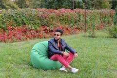 Araber Guy Musingly Looks Aside, Rest und Sitzen im Stuhl in Gree Lizenzfreies Stockfoto