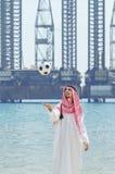 Araber mit footbal an der Küste Stockfotografie