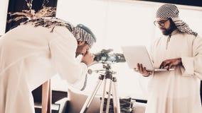 Araber som ser på teleskopet och rymmer bärbara datorn arkivfoto