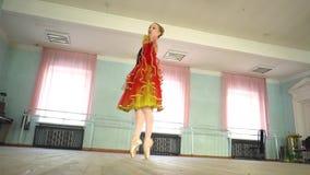 Ballerina in a ballet hall. Arabesque. Classical Ballet dancer side view. Beautiful graceful ballerine in black practice ballet position near large window in stock video