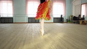 Ballerina in a ballet hall. Arabesque. Classical Ballet dancer side view. Beautiful graceful ballerine in black practice ballet position near large window in stock video footage