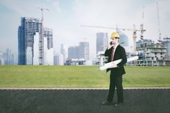 Arabian architect walking near construction sites. Image of Arabian male architect talking on the mobile phone while carrying blueprints and walking near Royalty Free Stock Photo