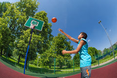 Arabian boy with ball flying to basketball goal. On the playground outside during sunny summer day royalty free stock image