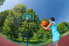 Arabian boy holds ball to throw in basketball goal. On the playground outside during sunny summer day stock images