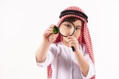 Arabian boy in keffiyeh examines precious stone. Through magnifying glass. Isolated on white background. Studio portrait royalty free stock photo