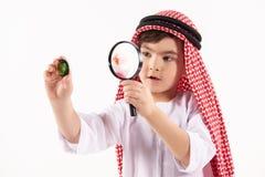 Arabian boy in keffiyeh examines precious stone. Through magnifying glass. Isolated on white background. Studio portrait royalty free stock image