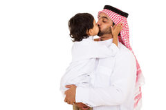 Arabian boy kissing father. Lovely arabian boy kissing his father isolated on white Royalty Free Stock Images