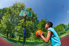 Arabian boy ready to throw ball in basketball goal Royalty Free Stock Photos