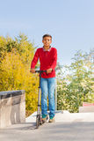 Arabian boy in red shirt stands on push-bicycle. Arabian boy in red long sleeve shirt stands on push-bicycle during sunny autumn day Stock Photos