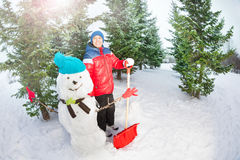 Arabian boy with shovel standing near snowman Stock Photo