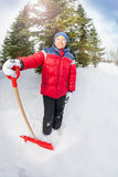 Arabian boy with shovel in winter during day Stock Photos