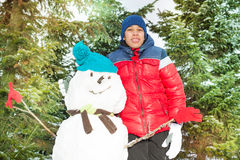 Arabian boy standing near snowman in winter Royalty Free Stock Images