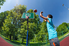 Arabian boy throws ball in basketball goal. On the playground outside during sunny summer day royalty free stock photo