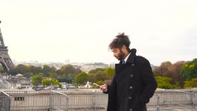 Arabian boy walking near Eiffel Tower with smartphone in slow motion. n. Handsome mulatto tourist using smartphone and enjoying France travel in slow motion stock video