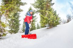 Arabian boy working with shovel and cleaning snow Stock Photos