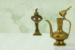 Arabian brass ware. A bright table top with a old brass arabic teapot in front of abstract blurred background. Space. stock photography