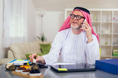 Arabian business man in his home office. Using smart phone Royalty Free Stock Photography