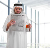 Arabian business man reading newspaper. In office Royalty Free Stock Images