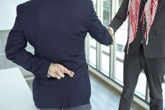 Arabian Business man shaking hand with lie sign stock image