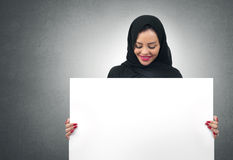 Arabian business woman holding a white board isolated