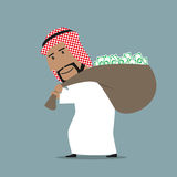 Arabian businessman carrying full money bag. Successful smiling cartoon arabian businessman carrying heavy and full of dollars bag. Wealth, success or abundance Royalty Free Stock Photos