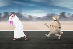 Arabian businessman is chased Trump word on track Stock Photos