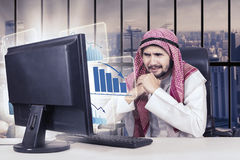 Arabian businessman and declining graph in office. Portrait of a confused male entrepreneur looking at the monitor with a virtual declining financial graph while Royalty Free Stock Photo