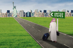 Arabian businessman getting out of the United States. Portrait of Muslim businessman getting out from the city with text of United States on a signpost while Stock Photos