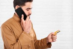 Arabian businessman keeps credit card and talks on the mobile phone. Royalty Free Stock Image