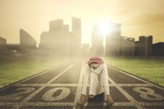 Arabian businessman kneeling in start position Royalty Free Stock Images