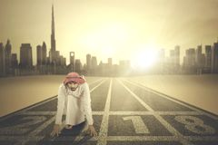 Arabian businessman kneeling on the track Stock Image