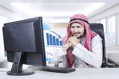 Arabian businessman looks frustrated with declining graph. Picture of a middle eastern businessman looks frustrated with a virtual declining graph on computer in Royalty Free Stock Photo