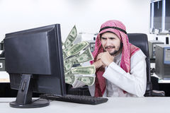 Arabian businessman looks unhappy with a computer Stock Photo